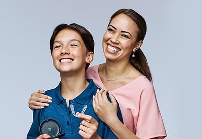 mum and son smiling with Invisalign in his hand